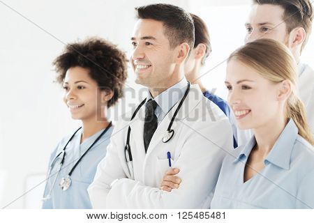 hospital, profession, people and medicine concept - group of happy doctors wit stethoscopes or mentor with interns at hospital