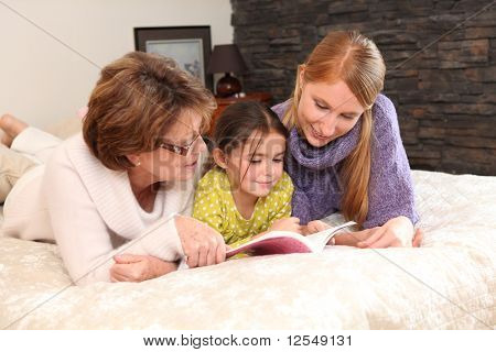 Portrait of two women and a little girl stretched out on a bed reading a book