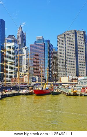 New York, USA - April 25, 2015: Ships in the harbor of South Street Seaport on East River. Lower Manhattan in New York USA is on the background. Pier 17. Tourists around.