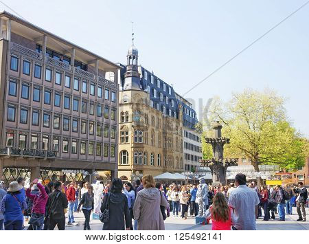 COLOGNE GERMANY - MAY 4 2013: Street view of the Cologne Cathedral Square with a fountain in Cologne in Germany. Domforum on Domplatte square. People around.