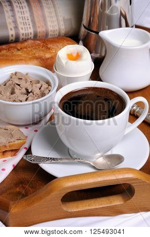 Breakfast on a tray with a cup of coffee toast with liver pate Soft-boiled egg and a newspaper
