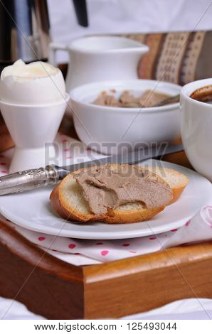 A slice of toast spread with liver pate for breakfast on a tray