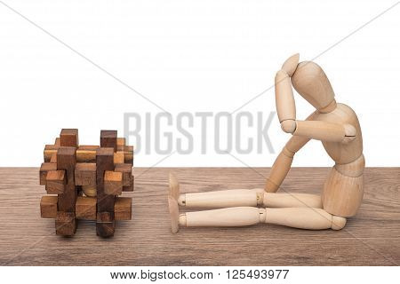 Wooden dummy thinks of the solution of a cube puzzle. Isolated on white background.