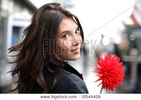 Mulher bonita com flor vermelha olhando para trás