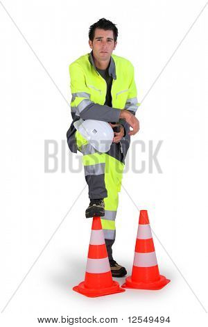 Portrait of a workman with a safety helmet and traffic cones