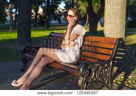 Beautiful emotional brunette girl laughing on the phone in the park summer glasses pink dress, enjoy your holiday in the city. Fashion style of life, a bright summer day.