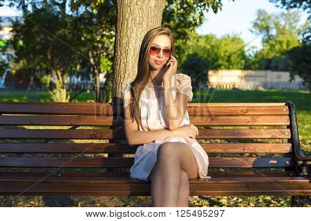 Beautiful brunette woman sitting on a park bench in summer. Talking on the phone. The pink dress, fashion style urban life. In the glasses tanned skin business woman resting after work.