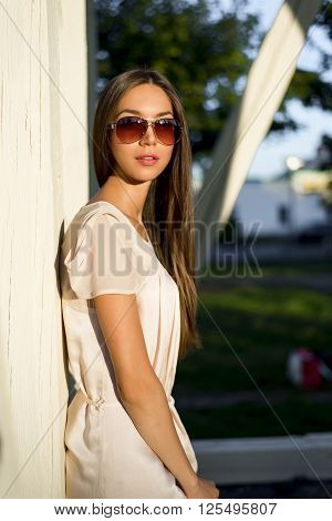 Outdoor fashion portrait glamor sensual young stylish woman in glasses, wearing a delicate summer dress outfit brunette girl. Pink dress, red lips tanned skin. Business lady resting outdoor near tree