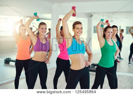 Close-up Of Group Of Young Women Doing Exercise With Dumbbells On Triceps
