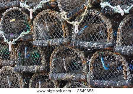 Lobster pots stacked on quayside forming a pattern