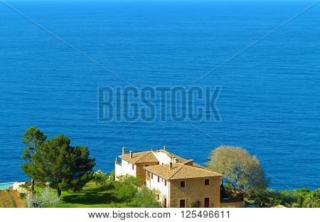 scenery with residential house overlooking the blue sea