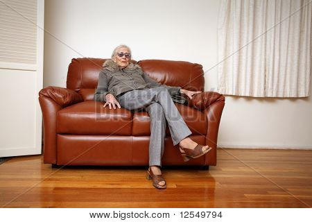 Senior Woman Sitting On Leather Sofa