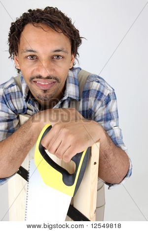 Portrait of a workman leaning on a board with a saw