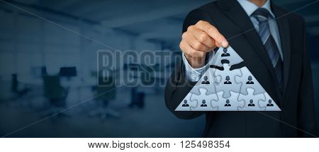 CEO leadership and corporate hierarchy concept - recruiter complete team represented by puzzle in pyramid scheme by one leader person (CEO). Wide banner composition with office in background.