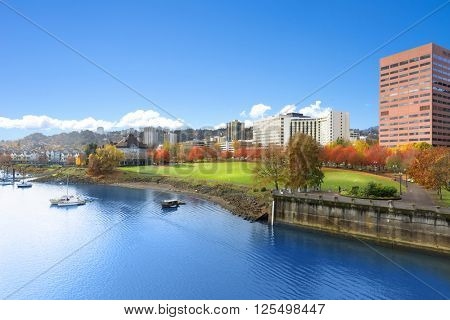 park near tranquil water with cityscape and skyline in portland