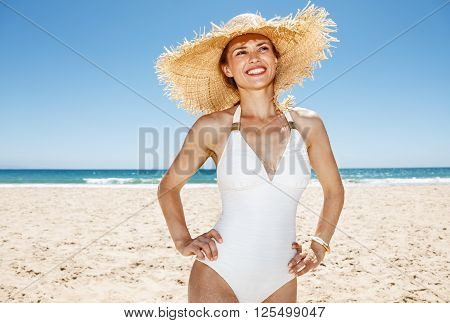 Happy Woman In Straw Hat At Beach Looking Into The Distance