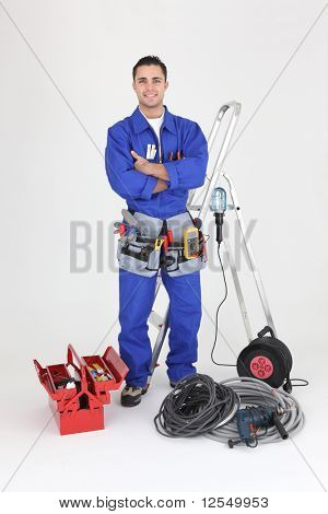 Young electrician smiling on white background