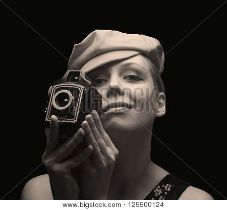 Sepia toned picture of a young blonde woman holding a retro photo camera and smiling