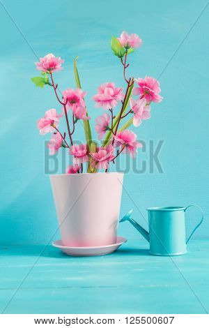 Artificial pink flower on a blue background.