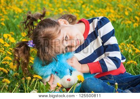 Little cute girl with pigtails sitting on the lawn with dandelions