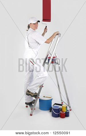 Portrait of a painter on a ladder painting a white wall