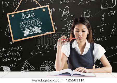 Thoughtful businesswoman reading against blackboard
