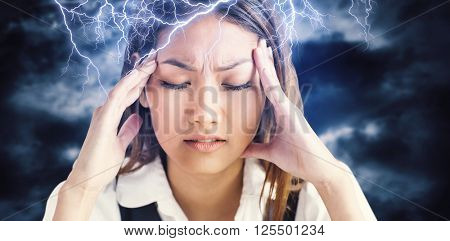 Nervous businesswoman holding her head against blue sky with white clouds