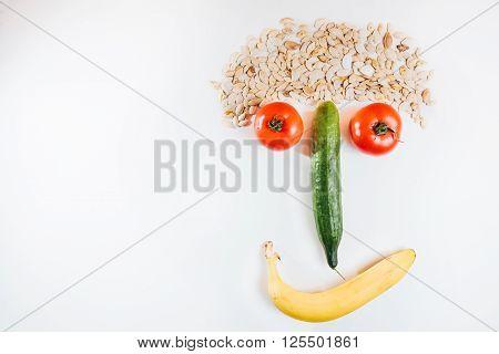 Happy face made with fresh fruits. Tomato cucumber banana pumpkin seeds. fruit face.joke.