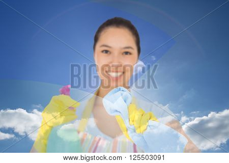 Happy woman wiping in front of her against blue sky with clouds and sun