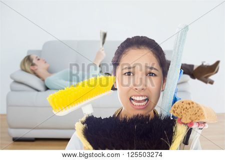 Very stressed woman with cleaning tools against attractive blonde woman reading newspaper lying on couch