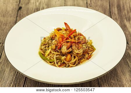 Fried Chinese noodles with vegetables and a cauliflower and with seafood