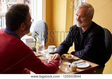 Male couple holding hands at restaurant, over shoulder view