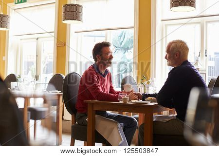 Male couple hold hands at a restaurant, three quarter length