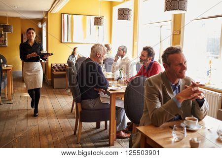 Customers at tables and waitress in busy restaurant interior