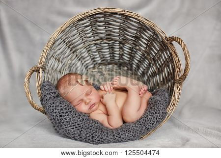 A newborn baby with a beige bow on her head, sleeping sweetly in the brown, round, wicker basket in soft grey knitted shawl,pursing his arms and legs,a portrait of a sleeping child on gray background