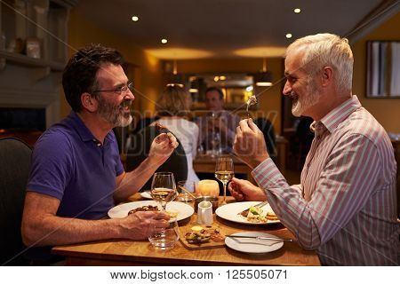 Middle aged male couple eating evening meal in a restaurant