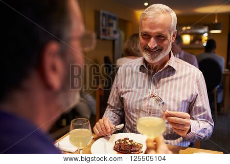 Male couple eating meal in a restaurant, over-shoulder view