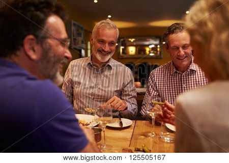 Four friends talking together during a meal at a restaurant