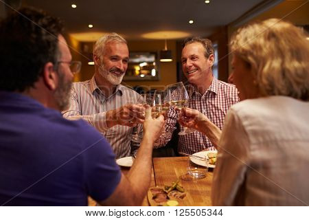Four friends making a toast during a meal at a restaurant