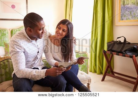 Young couple study a guide brochure together in a hotel room