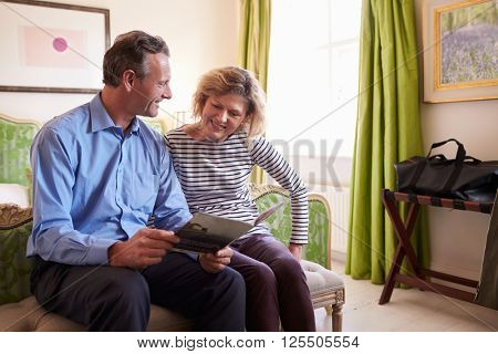 Senior couple study a guide brochure together in hotel room