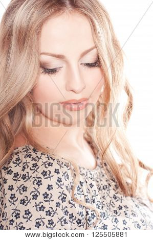 Beautiful blonde woman posing over white. Looking down. Wearing floral printed dress. Elegance.