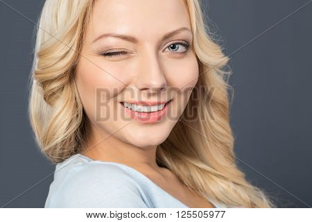 Give me a wink. Cheerful charming young girl smiling and winking while expressing positivity
