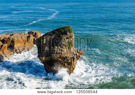 Pancake Rocks in Paparoa National Park New Zealand. Seascape with layered rock formation in form of cliff island. Punakaki is nature wonder and famous tourist destination of South Island New Zealand