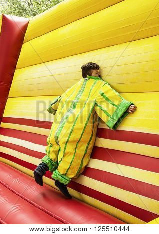 The boy in colorful plastic dress in the bouncy castle. Leisure activity.