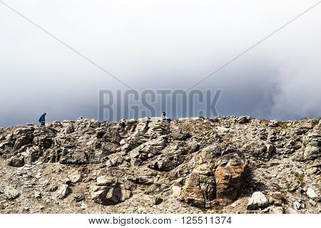 Two lonely tourists climbing in Switzerland mountains