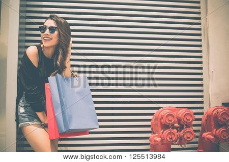 Pretty cheerful girl with shopping bags standing at the wall