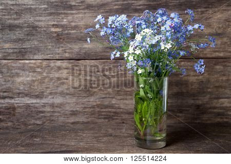 Forgetmenot flowers in vase on a wooden background