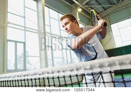 Low angle view of determined young man playing tennis indoor.