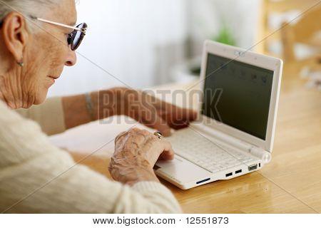 Mulher idosa digitando no computador portátil